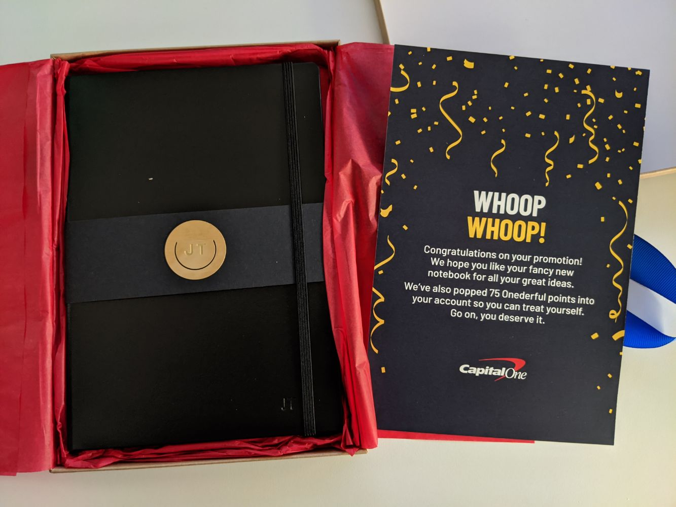 The inside of the parcel - on the right, a card with a congratulatory message inside it. On the left, a black notebook, embossed with Jamie's initials