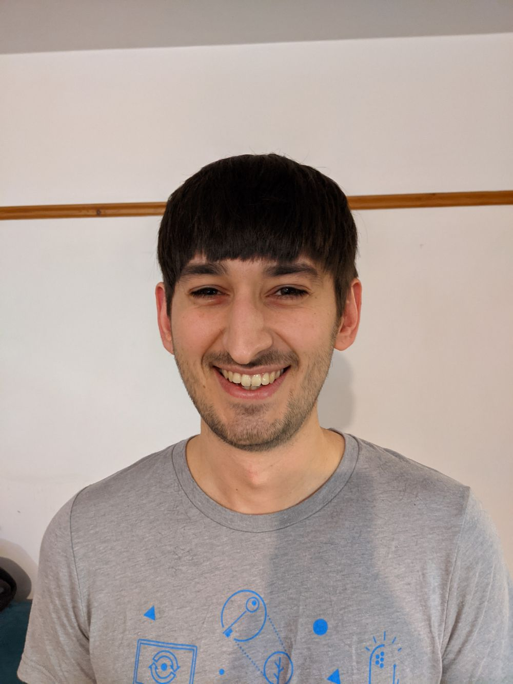 Photo of Jamie after the haircut, showing his beard very closely trimmed to just a bit more than stubble, with his hair up just above his eyebrows, with much more of his face now visible