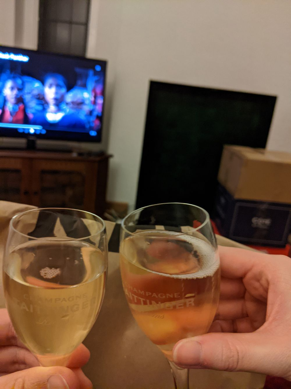 Jamie and Anna toasting to the new house with two Champagne flutes, in front of a bag of KFC, with Black Panther on the TV behind, next to boxes of yet-to-be-unpacked belongings
