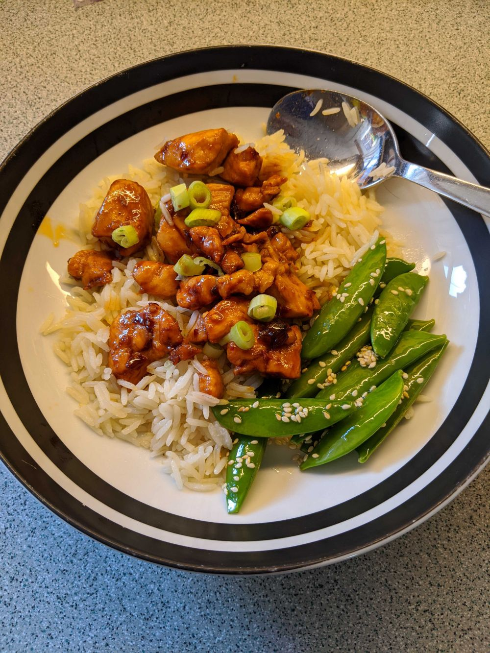 Chicken teriyaki with rice, spring onions, and sesame sugar snap peas, the chicken looking very sticky