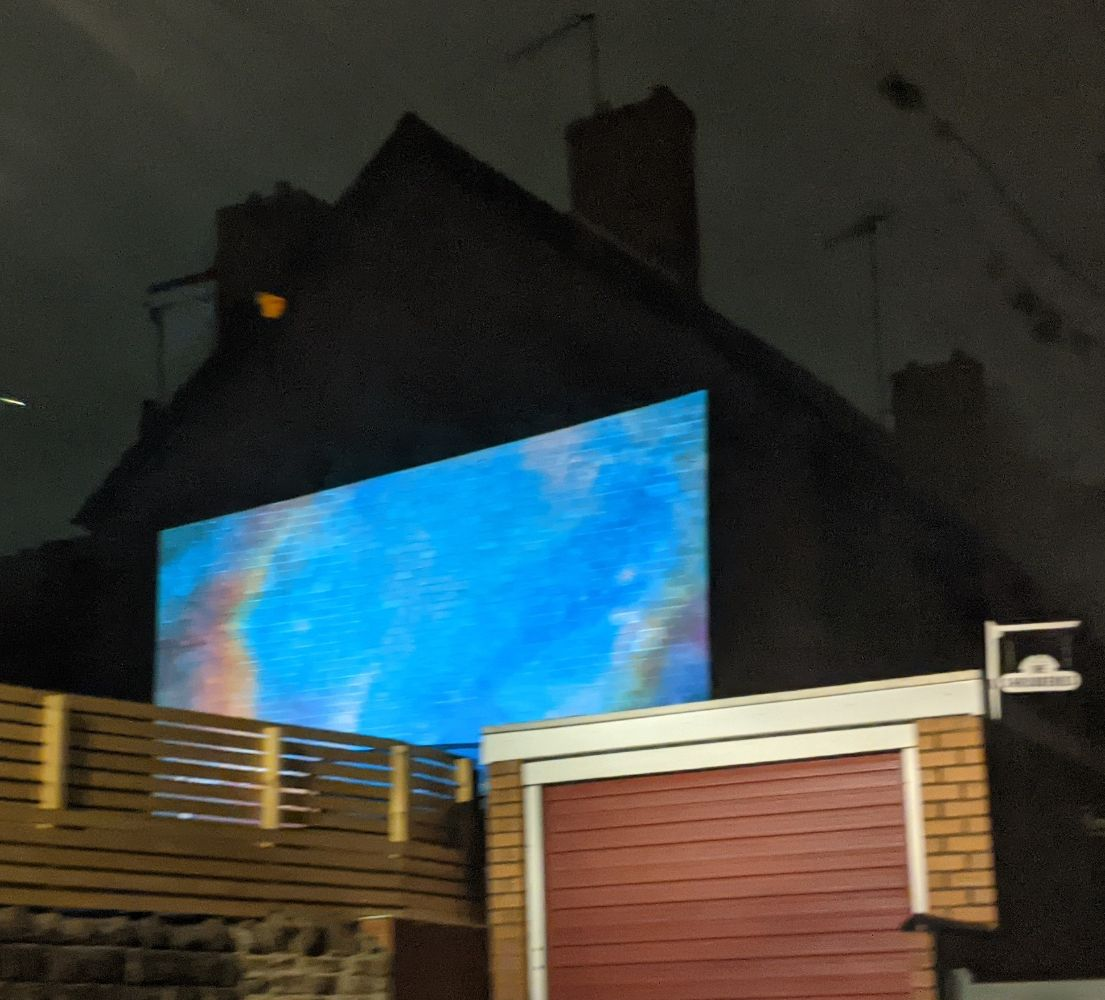 A projector using the side of the house to create a huge outside screen