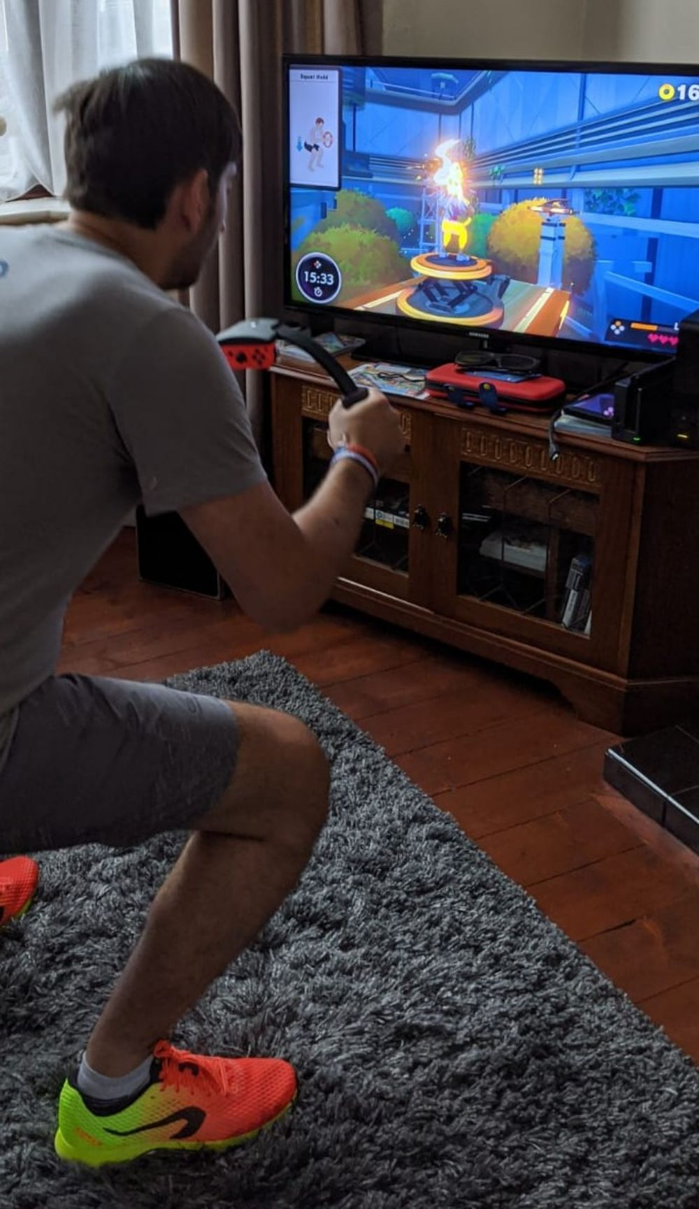 Jamie squatting, playing Ring Fit Adventures on the Nintento Switch, with his new trainers visible, with a fade from florescent orange to yellow