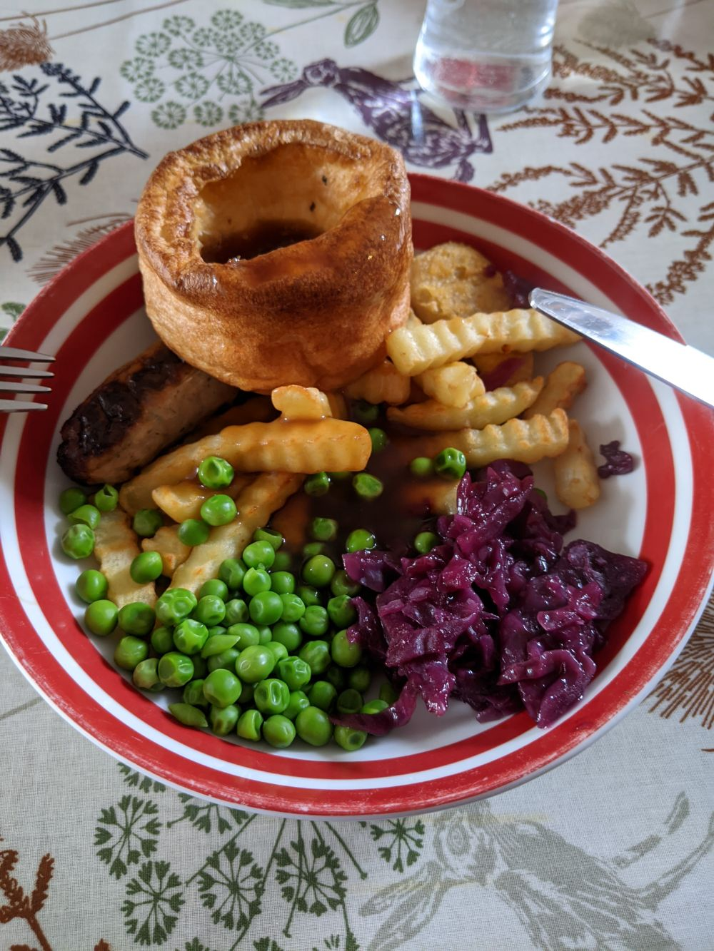 A dish with a beef dripping Yorkshire pudding, chips, a bacon and maple syrup sausage, red cabbage and peas, all covered in gravy