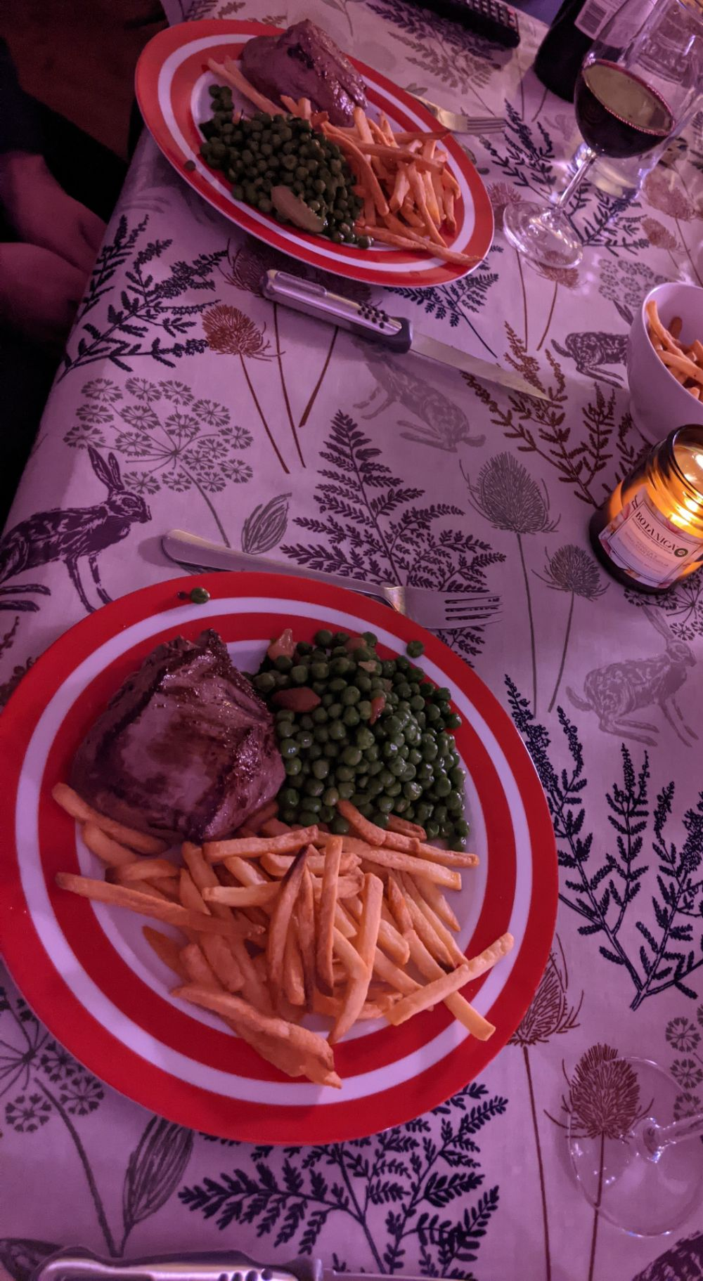 A slanted photo of a table set with two plates with a fillet steak (cooked blue / very very rare), minted peas, french fries, a bowl of overflow fries, and a large glass of Malbec