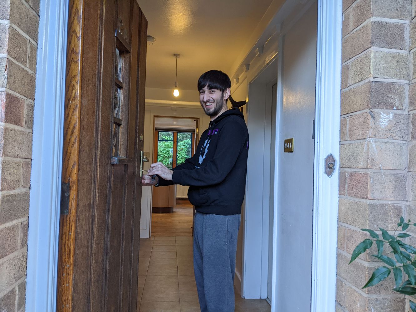 Jamie standing in the doorway of his house, with keys in hand, pretending to be opening it for the first time