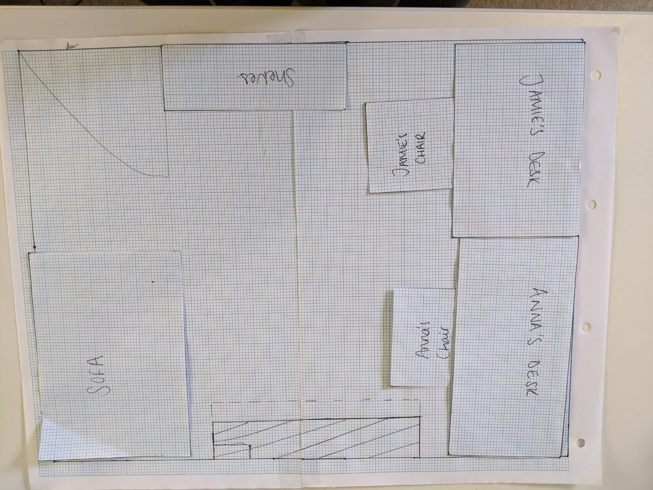 Floor plan of Jamie and Anna's desks right next to each other on one side of the room, with shelves behind Jamie and a sofa in the window