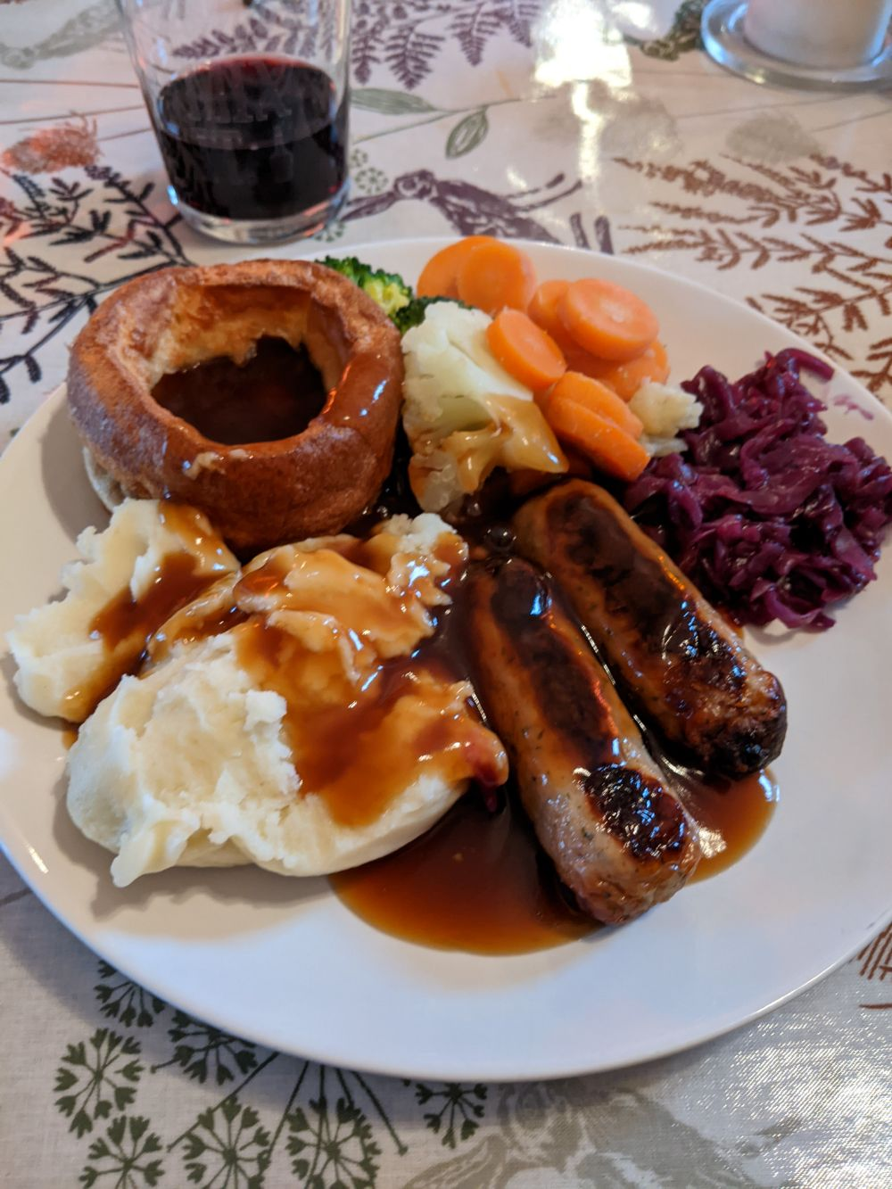 A plate with a beef dripping Yorkshire pudding, mashed potatoes, bacon and maple syrup sausages, red cabbage, carrots, cauliflower and broccoli, all covered in gravy, with a glass of red wine